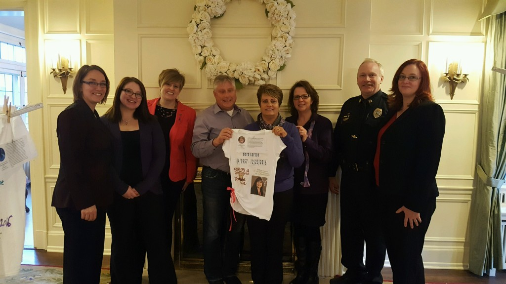 HOPE Center staffers and Faribault Police Department Captain Neal Pederson stand united with Barb Larson in honoring her memory. The family is holding the personalized t-shirt designed in Barb's memory for The Clothesline Project.
