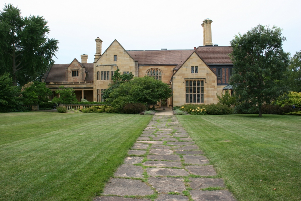 A sweeping lawn stretches between the gardens and the rear of the late 1920s mansion.