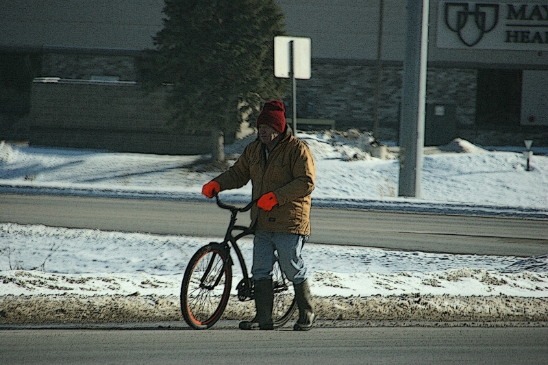 A man walks his bike along Minnesota State Highway 21 in Faribault on Sunday afternoon.