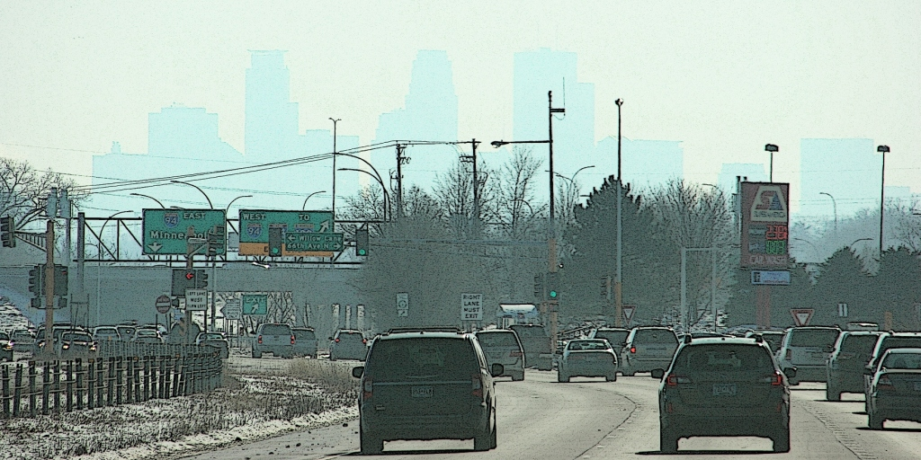 The outline of the Minneapolis skyline appears in the hazy distance while traveling along Minnesota State Highway 252.