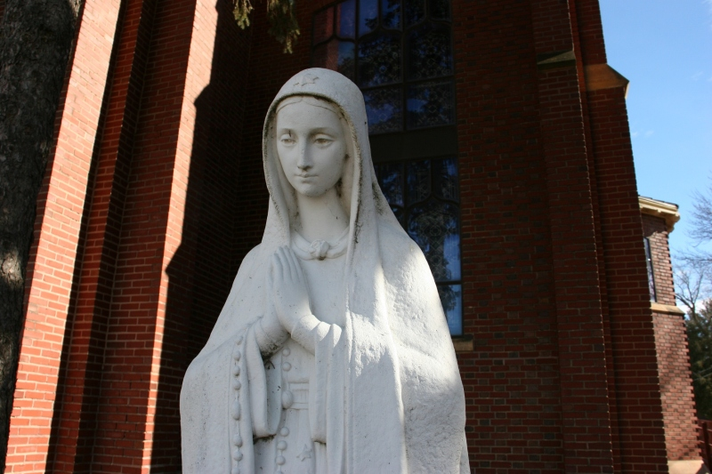 A statue of Mary outside the front of the church.