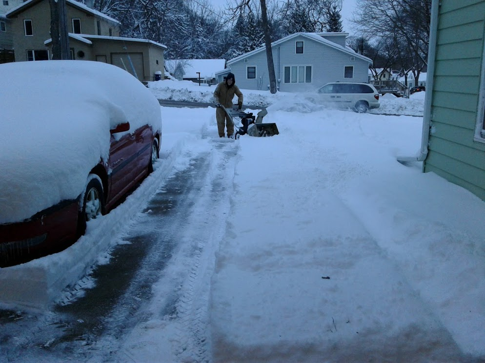 In the fading light of day, Randy works to blow snow from the driveway.