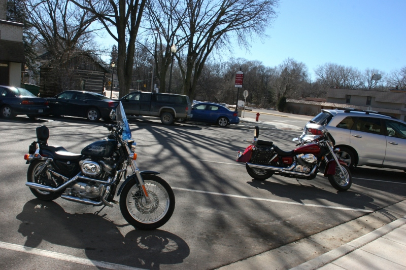 Two historic log cabins are situated downtown where bikers and others stopped on Saturday afternoon.